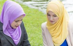 Deux étudiants universitaires ayant des idées de discussion et de changement tout en se reposant dans le parc Photo libre de droits