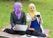 Deux étudiants universitaires ayant des idées de discussion et de changement tout en se reposant dans le parc Photographie stock libre de droits