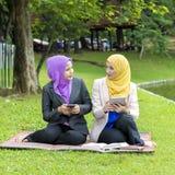 Deux étudiants universitaires ayant des idées de discussion et de changement tout en se reposant dans le parc Photos stock