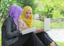 Deux étudiants universitaires ayant des idées de discussion et de changement tout en se reposant dans le parc Photos libres de droits