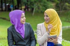 Deux étudiants universitaires ayant des idées de discussion et de changement tout en se reposant dans le parc Image stock