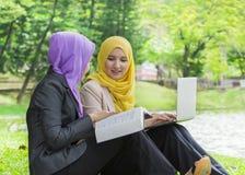 Deux étudiants universitaires ayant des idées de discussion et de changement tout en se reposant dans le parc Images stock