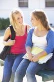 Deux étudiants universitaires féminins à l'extérieur du bâtiment de campus Photographie stock