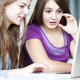 Deux étudiants universitaires féminins travaillant sur un ordinateur portatif Image libre de droits