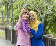 Deux étudiants universitaires prenant la photo en parc photos stock