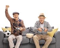 Deux aînés jouant le jeu vidéo du football Image stock