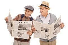 Deux aînés lisant les actualités ensemble Photos libres de droits