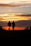 Deux aînés silhouettés marchant dans le coucher du soleil Photographie stock