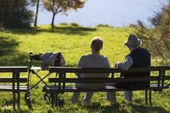 Deux aînés sur le banc sur un lac ensoleillé Photos libres de droits