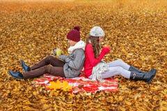 Deux adolescente et garçon s'asseyant en parc sur un plaid soutient entre eux et conserve le thé potable chaud Image libre de droits