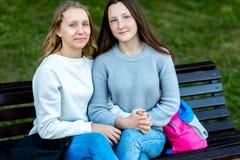 Deux adolescentes Été sur un banc dans la ville après école Repos heureux se tenant mains du ` s Le concept est le meilleur Photos libres de droits