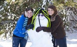 Deux adolescentes avec le bonhomme de neige photographie stock