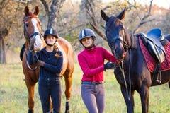 Deux adolescentes avec leur cheval en parc Photographie stock libre de droits