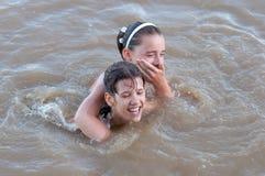 Deux adolescentes ayant l'amusement dans le fleuve Image stock