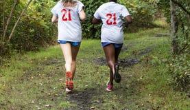 Deux adolescentes courant dans les bois photos stock