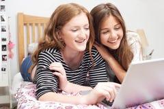 Deux adolescentes dans la chambre à coucher regardant l'ordinateur portable Images libres de droits