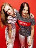 Deux adolescentes de meilleurs amis ayant ensemble l'amusement, pose émotive sur le fond rouge, sourire heureux de besties, mode  Photos stock