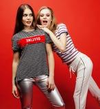 Deux adolescentes de meilleurs amis ayant ensemble l'amusement, pose émotive sur le fond rouge, sourire heureux de besties, mode  Photo libre de droits