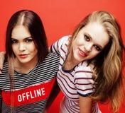 Deux adolescentes de meilleurs amis ayant ensemble l'amusement, pose émotive sur le fond rouge, sourire heureux de besties, mode  Photos libres de droits