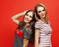 Deux adolescentes de meilleurs amis ayant ensemble l'amusement, pose émotive sur le fond rouge, sourire heureux de besties, mode  Photo stock