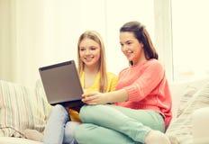 Deux adolescentes de sourire avec l'ordinateur portable à la maison Image libre de droits