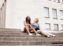 Deux adolescentes devant le bâtiment d'université souriant, ayant Image stock