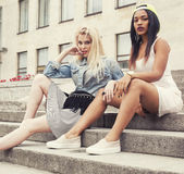 Deux adolescentes devant le bâtiment d'université souriant, ayant l'amusement, concept de personnes de mode de vie Image stock