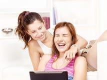 Deux adolescentes heureuses à l'aide de l'ordinateur de touchpad Photos stock