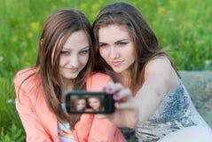 Deux adolescentes heureuses prenant la photo de lui-même avec le téléphone portable Images stock
