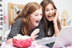 Deux adolescentes observant le film sur l'ordinateur portable dans la chambre à coucher photo libre de droits