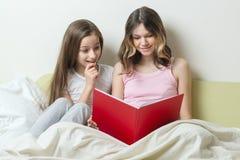 Deux adolescentes s'asseyant à la maison dans le regard de lit dans le carnet d'école Communication et étude à la maison images stock