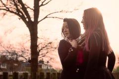 Deux adolescentes se tenant dehors au coucher du soleil Photos stock