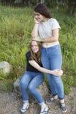 Deux adolescentes sont des meilleurs amis étreignant à la clairière nature Images libres de droits