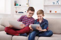 Deux adolescents à l'aide du comprimé sur le divan à la maison Photographie stock
