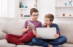 Deux adolescents à l'aide du comprimé sur le divan à la maison Photographie stock libre de droits