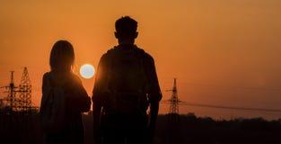 Deux adolescents attendent avec intérêt le coucher du soleil d'un grand soleil au-dessus de la ville photographie stock libre de droits