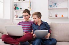 Deux adolescents avec des instruments sur le divan à la maison Photo stock