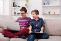 Deux adolescents avec des instruments sur le divan à la maison Photographie stock