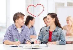 Deux adolescents avec les carnets et le livre à l'école Photo stock