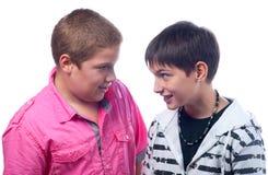 Deux adolescents ayant l'amusement d'isolement sur le fond blanc Photographie stock libre de droits