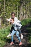 Deux adolescents d'amies de soeurs se montant ayant l'amusement dans le parc Photos stock