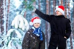 Deux adolescents dans des chapeaux Santa Claus de Noël ayant l'amusement dans le Sn Photographie stock libre de droits