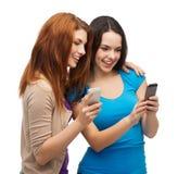Deux adolescents de sourire avec des smartphones Image stock