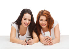 Deux adolescents de sourire avec des smartphones Photographie stock libre de droits
