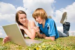 Deux adolescents de sourire avec l'ordinateur portatif photos stock