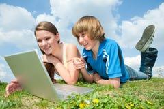 Deux adolescents de sourire avec l'ordinateur portatif Photographie stock libre de droits