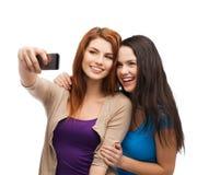 Deux adolescents de sourire avec le smartphone Image stock