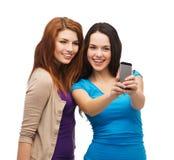 Deux adolescents de sourire avec le smartphone Photographie stock
