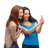 Deux adolescents de sourire avec le smartphone Photographie stock libre de droits
