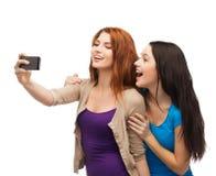 Deux adolescents de sourire avec le smartphone Photos libres de droits